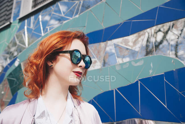 Redhead young woman wearing sunglasses against mosaic wall — Stock Photo