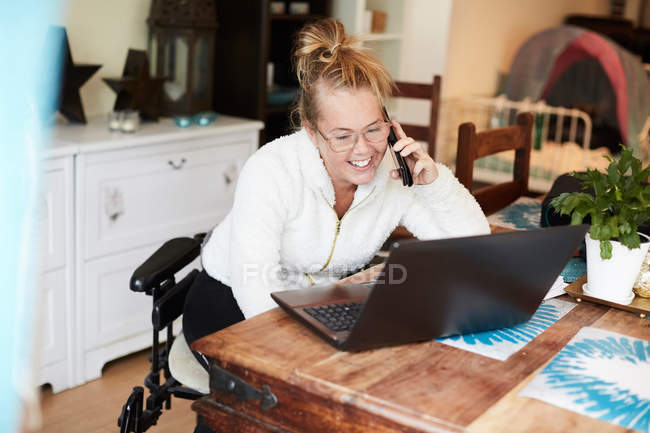 Smiling disabled woman talking on mobile phone while looking at laptop in house — Stock Photo