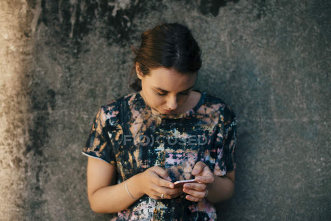 Young woman using mobile phone against wall — Stock Photo