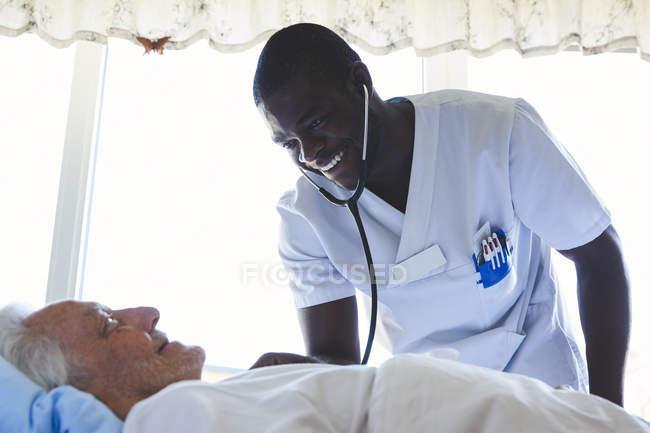 Счастливый мыжская нюна, изучив старший мужчина с стетоскоп в больничной палате — стоковое фото