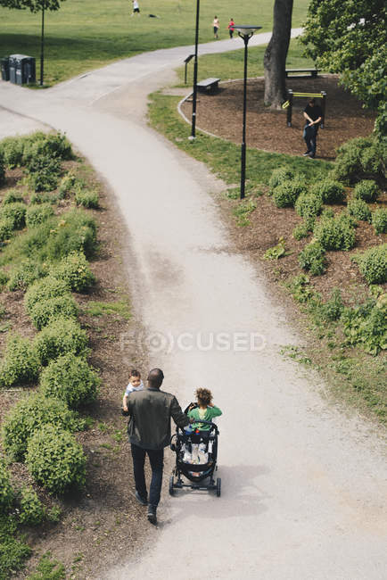 High angle view of man with children walking on pathway towards park — Stock Photo