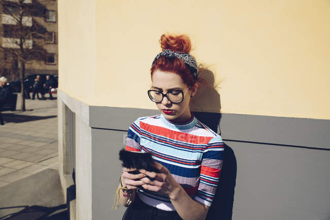 Young woman using mobile phone while standing against wall — Stock Photo