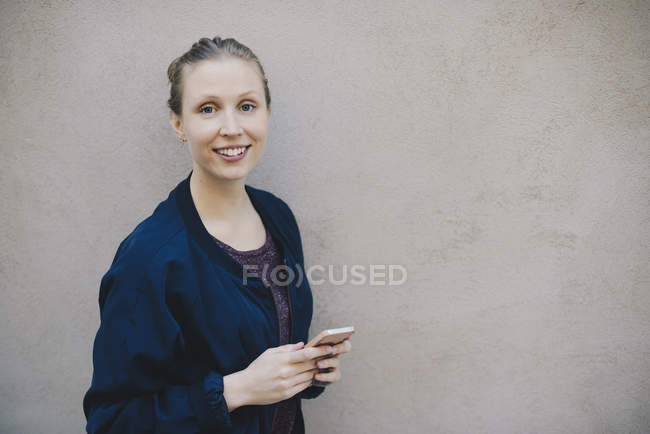 Portrait of happy female computer programmer holding smart phone while standing against beige wall in office — Stock Photo