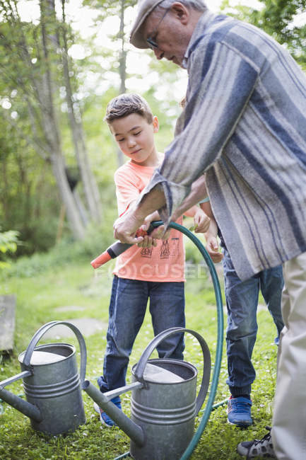 Grandfather holding garden hose with grandsons by watering cans in back yard — Stock Photo