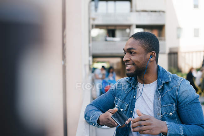 Smiling young man listening to earphones while standing on footbridge in city — Foto stock