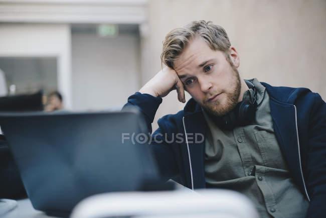 Fatigué d'informaticien utilisant l'ordinateur portable au bureau — Photo de stock