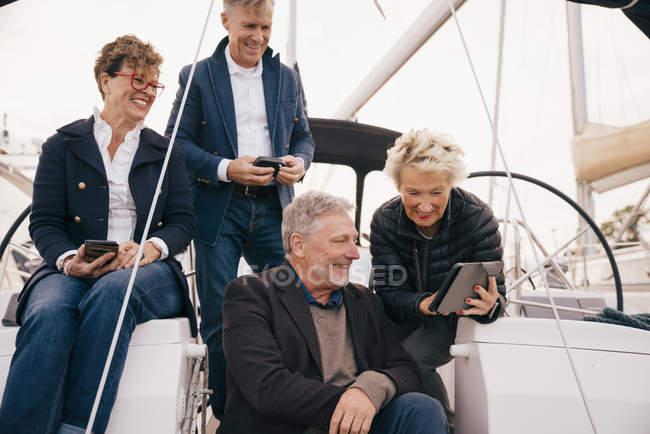 Casal sênior usando tablet digital enquanto viaja com amigos em iate — Fotografia de Stock
