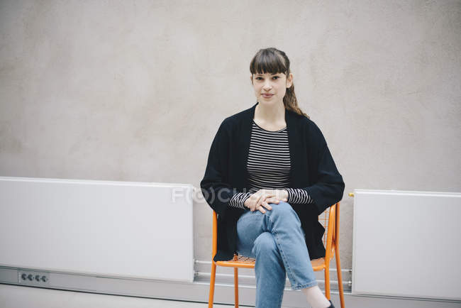Portrait of confident female computer programmer sitting on chair against beige wall in office — Stock Photo