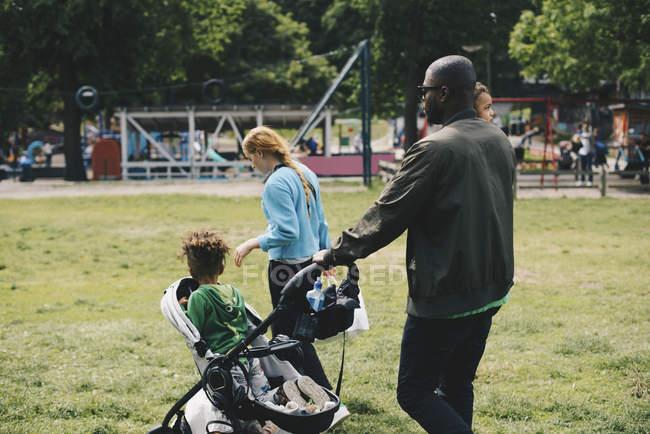 Family walking on grassy field at park — Stock Photo
