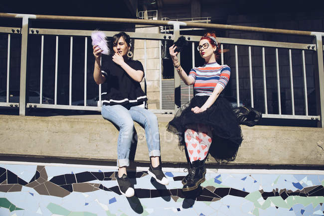 Hipster female friends taking selfie with mobile phones while sitting on wall against railing — Stock Photo