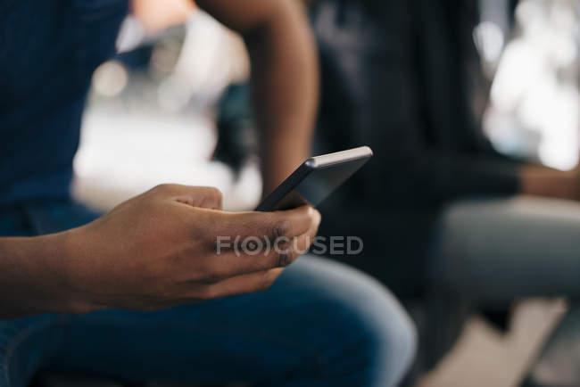 Immagine ritagliata di un giovane che usa lo smartphone in città — Foto stock