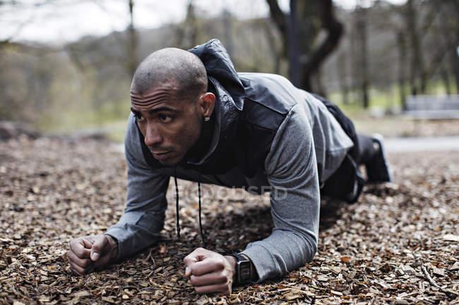 Determinato atleta maschio eseguire plancia posizione nella foresta — Foto stock