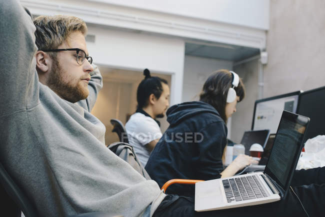 Side view of computer programmers working in office — Stock Photo