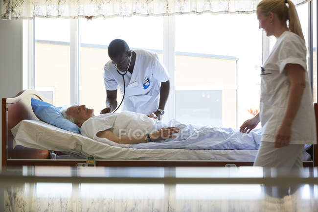 Enfermera mirando hombre colega examinando a hombre senior en sala de hospital - foto de stock