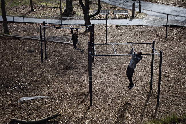 High angle view of male and female athletes hanging from monkey bars in forest — Stock Photo