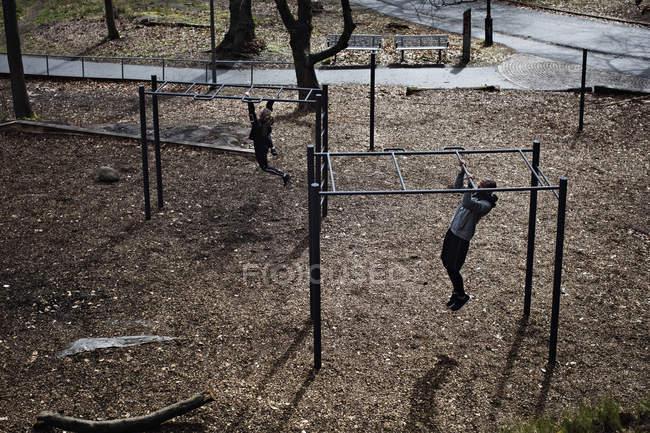 Vista de ángulo alto de atletas masculinos y femeninos cuelgan de barras en bosque - foto de stock