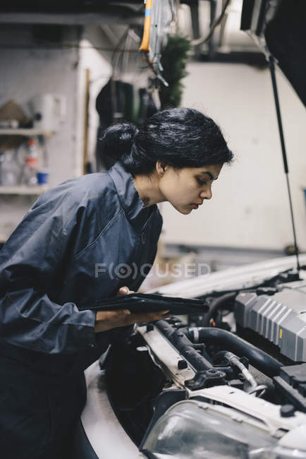 Side view of female mechanic holding digital tablet while examining car engine in auto repair shop — Stock Photo