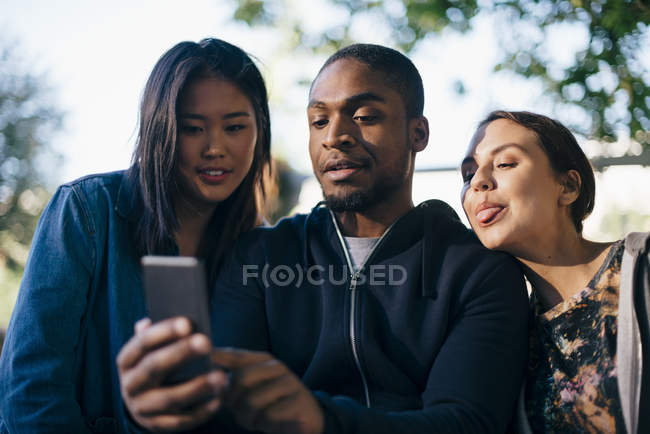 Low angle view of man taking selfie with female friends — Stock Photo