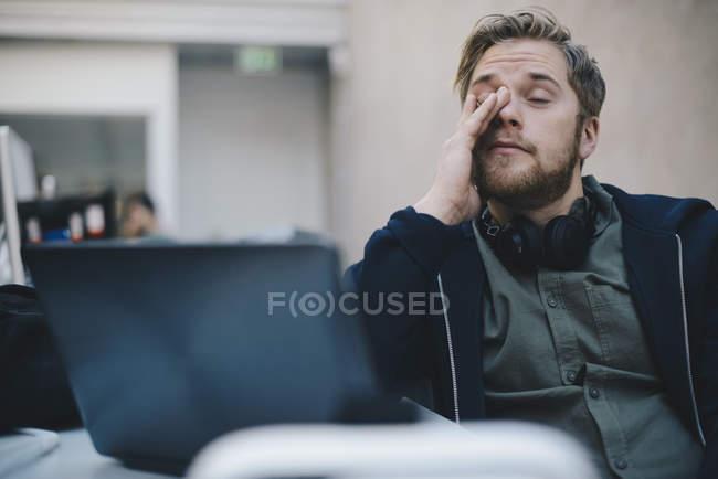 Programador de computador cansado, esfregando os olhos enquanto está sentado no escritório — Fotografia de Stock
