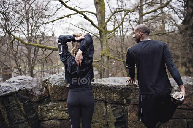 Вид сзади мужского и женского пола спортсменов, делать упражнения на растяжку, окружающие стены — стоковое фото