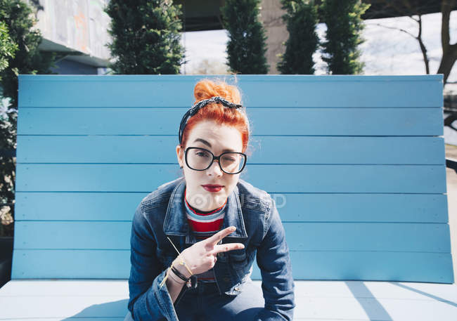Portrait of redhead young woman gesturing peace sign while sitting on bench — Stock Photo