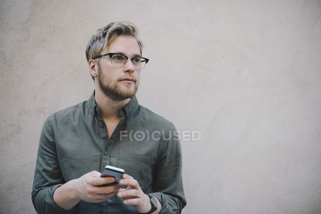 Thoughtful male computer programmer holding smart phone against beige wall in office — Stock Photo