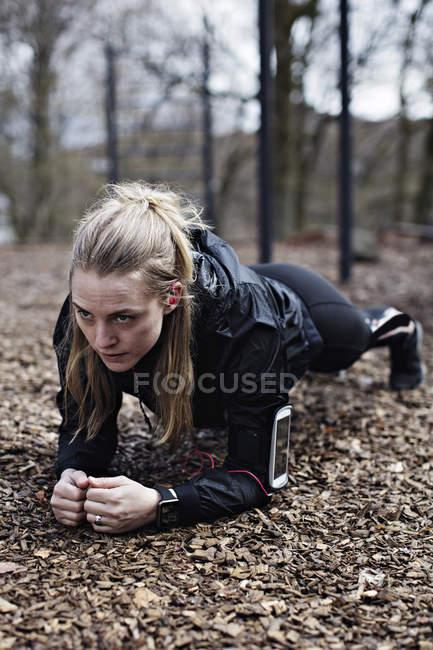 Determinato atleta femminile eseguire plancia posizione nella foresta — Foto stock
