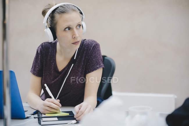 Жіночий програміст фотографіях хтось дивитися вбік одночасно набираючи текст на клей Примітка в офісі — стокове фото