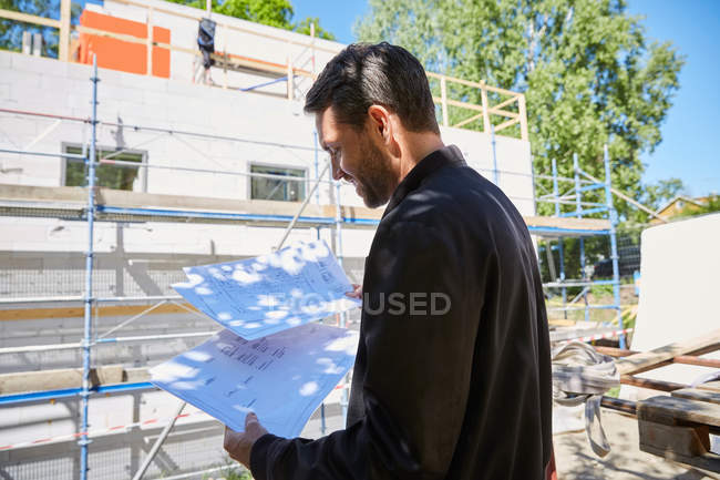 Businessman reading blueprints while standing at construction site on sunny day — Stock Photo