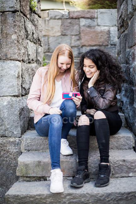 Amici femminili allegri che condividono smartphone mentre sono seduti sui gradini — Foto stock