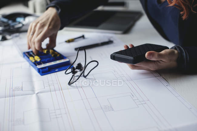 Midsection of female engineer holding portable hard drive on desk — Stock Photo