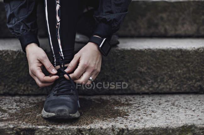Низький розділ людини прив'язки шнурок на дії. — стокове фото