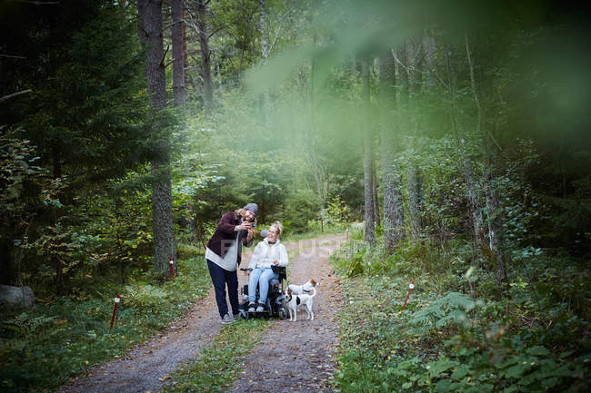 Male caretaker taking selfie with disabled woman in forest — Stock Photo