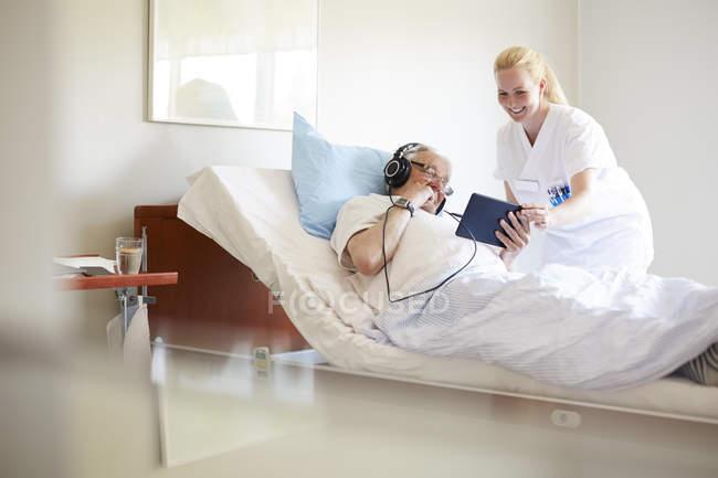 Happy female nurse assisting senior man in using digital tablet on hospital bed — Stock Photo