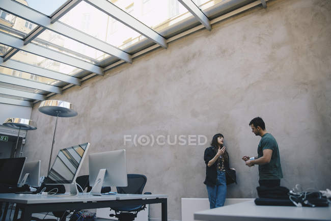 Low angle view of computer programmers discussing against wall in office — Stock Photo