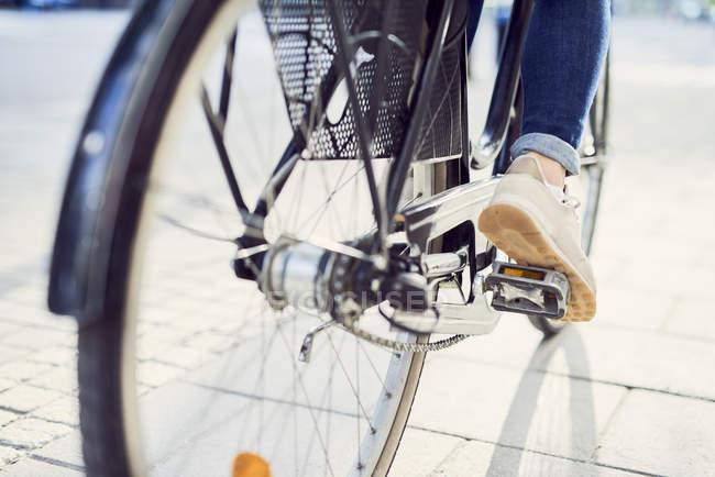 Mittlere erwachsene Frau radelt auf Fußweg — Stockfoto