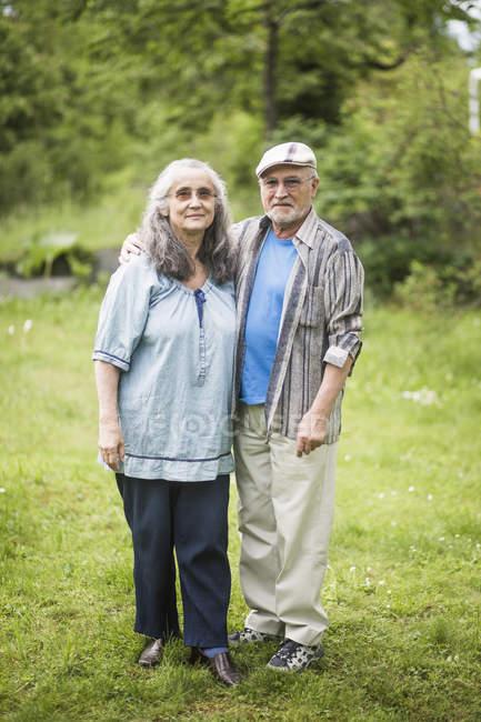 Retrato de pareja de ancianos de pie sobre hierba en el patio trasero - foto de stock