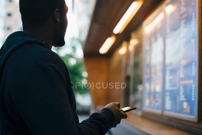 Vista laterale del giovane che guarda il menu mentre tiene lo smartphone — Foto stock