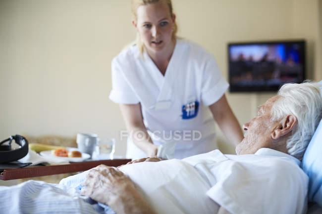 Female nurse serving breakfast to senior man in hospital ward — Stock Photo