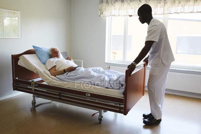Male nurse adjusting bed while senior man watching TV in hospital ward — Stock Photo