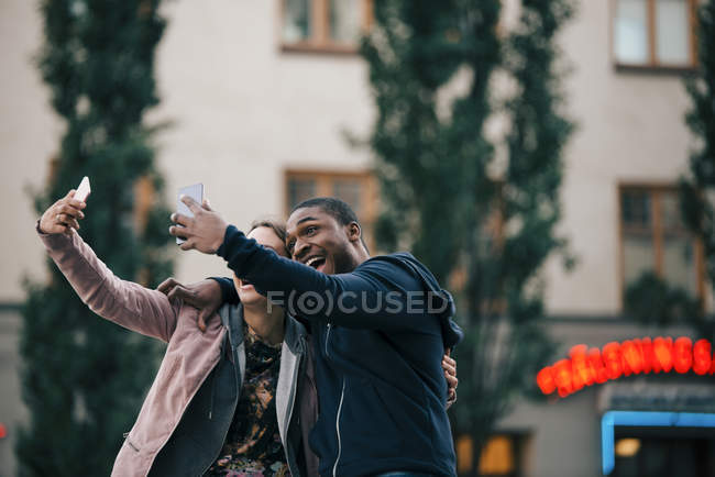 Cheerful young friends taking selfie from smart phones while standing against building — Foto stock