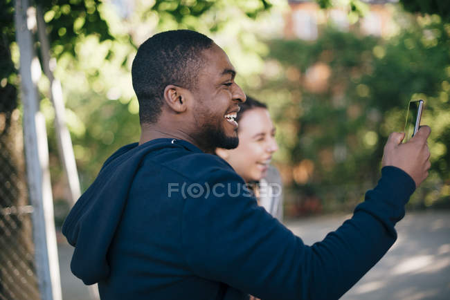 Side view of cheerful man photographing from smart phone — Stock Photo