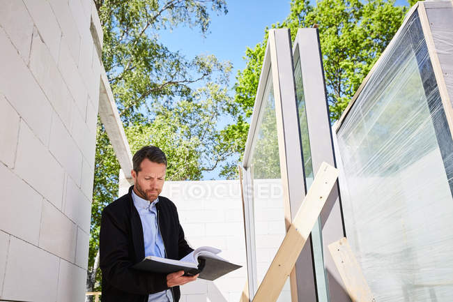 Low angle view of architect reading document while standing at construction site — Stock Photo