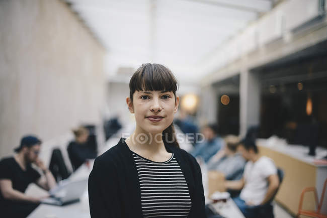 Portrait of female confident computer programmer at office with colleagues working in background — стокове фото
