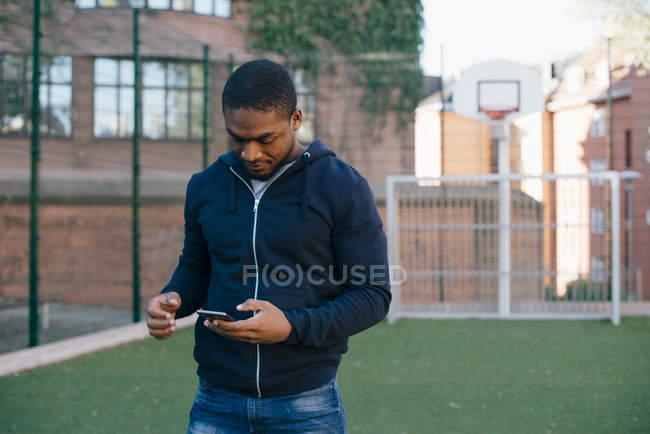 Giovane uomo in piedi sul campo di gioco durante l'utilizzo di smartphone — Foto stock