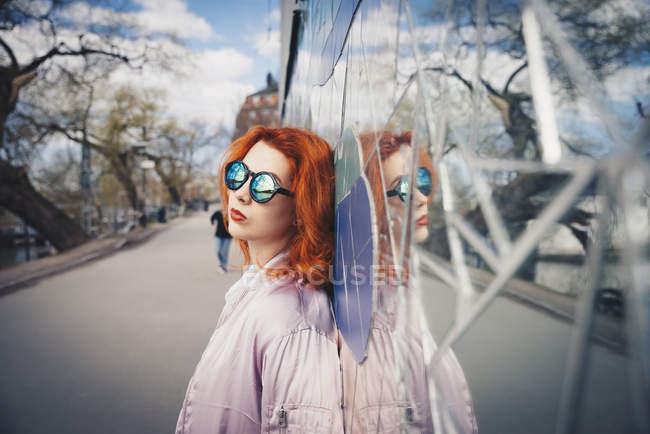 Redhead young woman wearing sunglasses while leaning on mosaic wall by street — Stock Photo