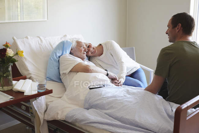 Couple visiting senior man in hospital — Stock Photo