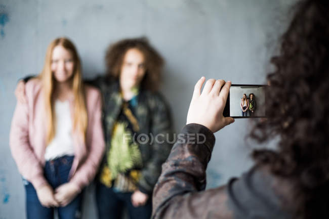 Teenage girl photographing friends standing against wall at parking garage — Stock Photo