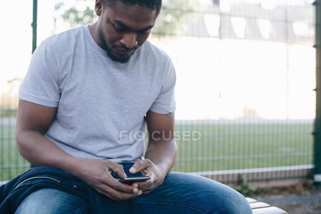 Giovane utilizzando smart phone mentre seduto sulla panchina contro la recinzione — Foto stock