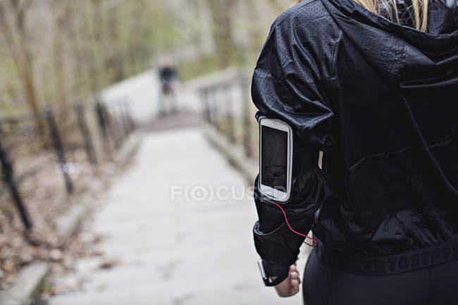 Sezione centrale della donna in forma con smart phone sulla fascia del braccio — Foto stock